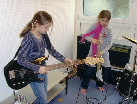 Zwei Mädchen sind beim proben mit ihren Gitarren.